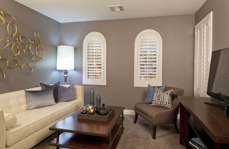 Charlotte family room with arced plantation shutters.