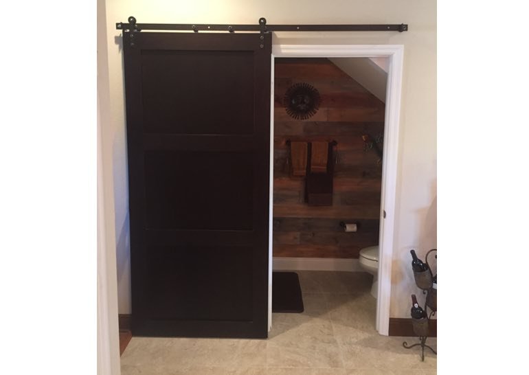 Dark brown barn door used as bathroom door