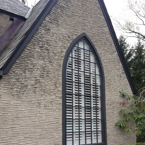 Exterior face of stone home with plantation shutters