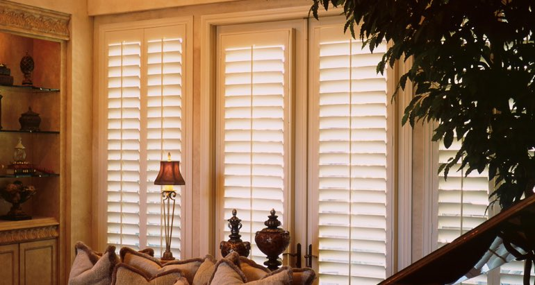 Plantation shutters on windows and door in Charlotte parlor