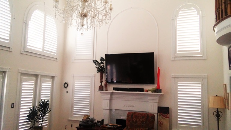 Charlotte great room with mounted television and arched windows.