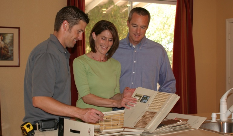 Homeowners choosing between samples of window treatments.