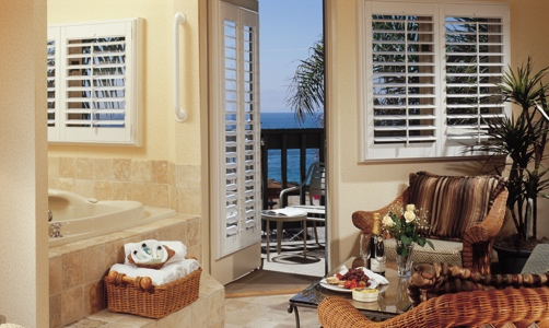 Plantation shutters on casement windows in a lakefront home.