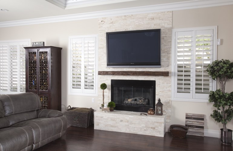 White plantation shutters in a Charlotte living room with plank hardwood floors.