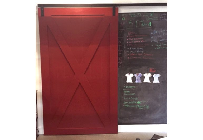 Bright red sliding barn door with black hardware next to chalkboard