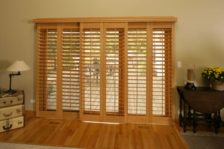 Wood shutters on sliding door leading to full porch.