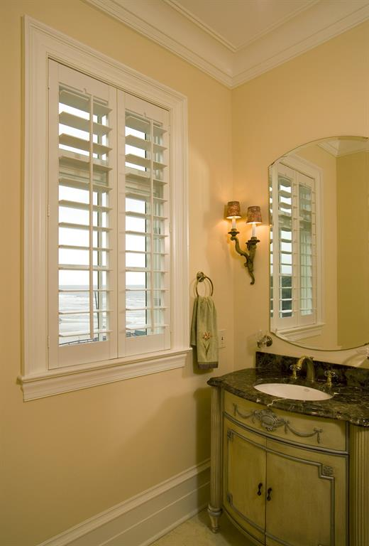 White plantation shutters in a bathroom outlooking the ocean