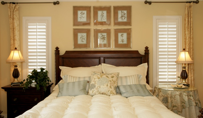 Bedroom with two tall plantation shutters on either side of bed in Charlotte